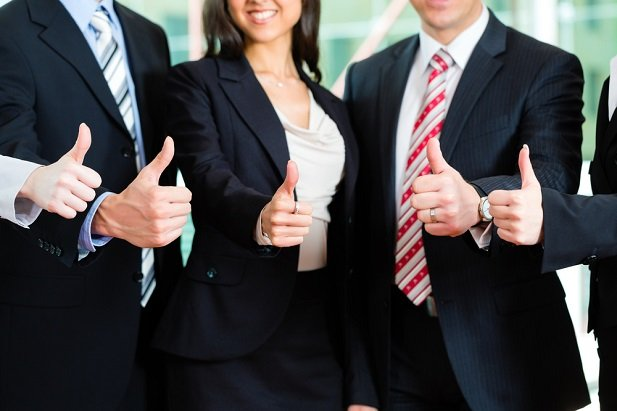 4 business people with thumbs up