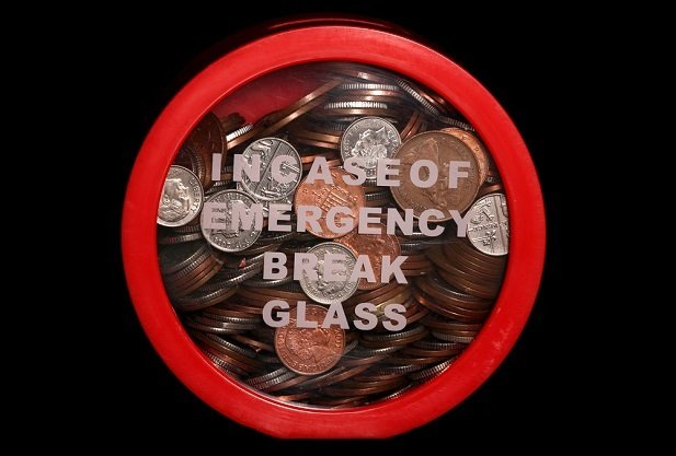 coins behind glass with words break in emergency only