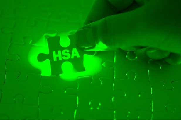 hand inserting HSA puzzle piece on green background