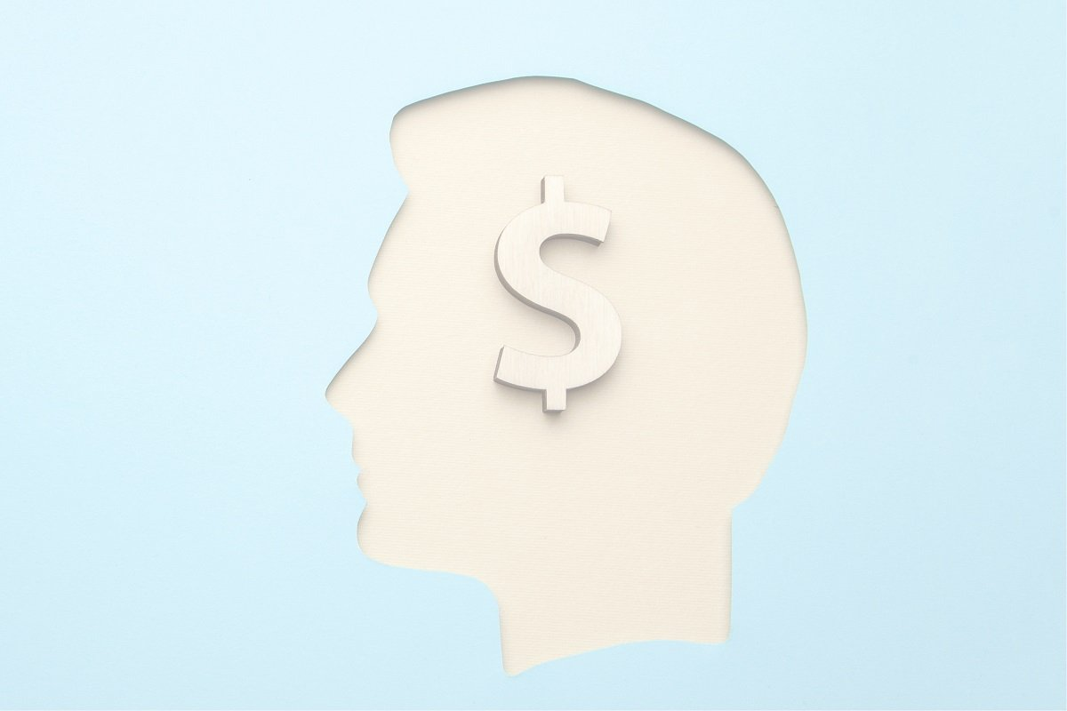 cutout of man's head with dollar sign