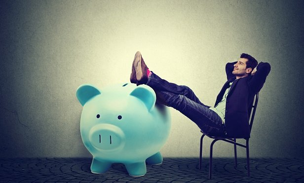 Man with feet propped up on piggy bank