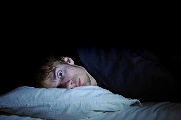 man in bed with one eye open