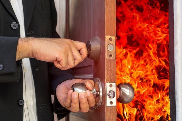 business man closing door on flames