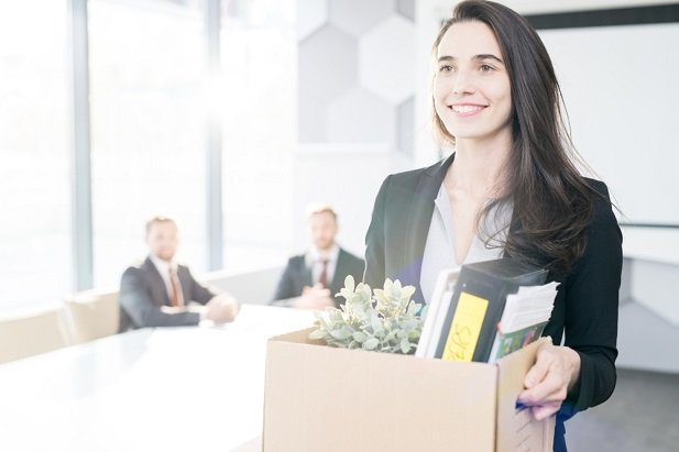 happy woman leaving work with box of belongings