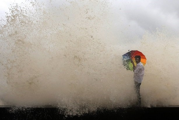 man with umbrella and ocean wave breaking over him