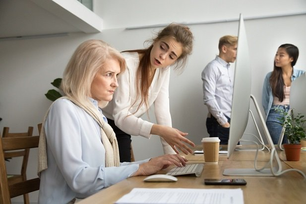 older woman at computer corrected by younger woman