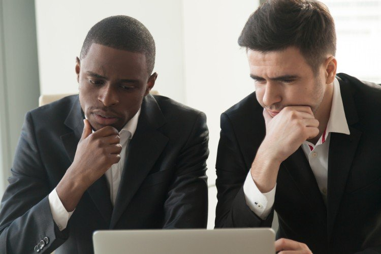 two businessmen staring at computer