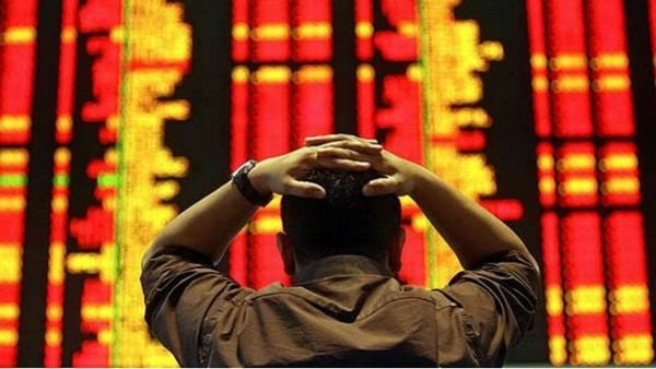 man with hands on head looking at stock market ticker
