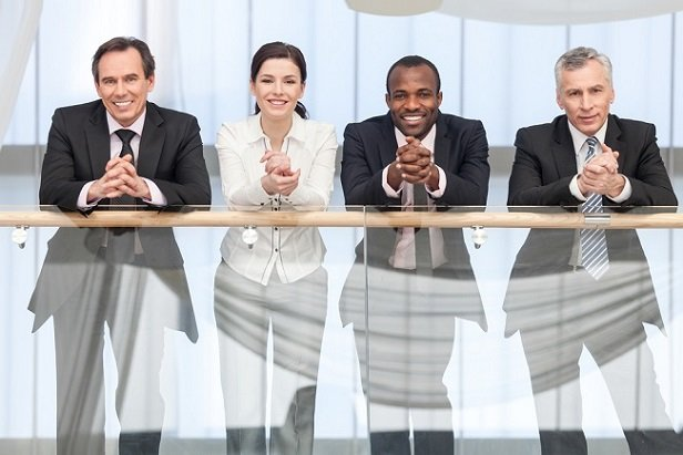 4 business people leaning over a railing smiling