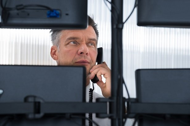 man on phone looking at 4 computer screens