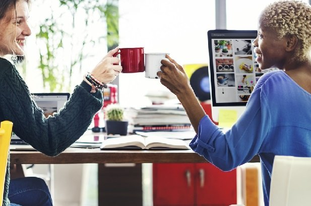 two women toasting coffee mugs