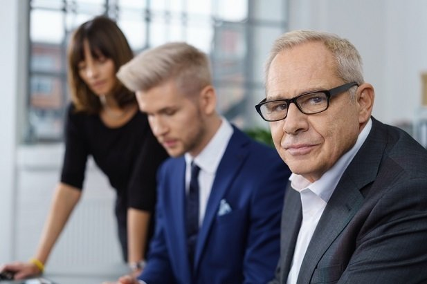 older man in office looking at camera