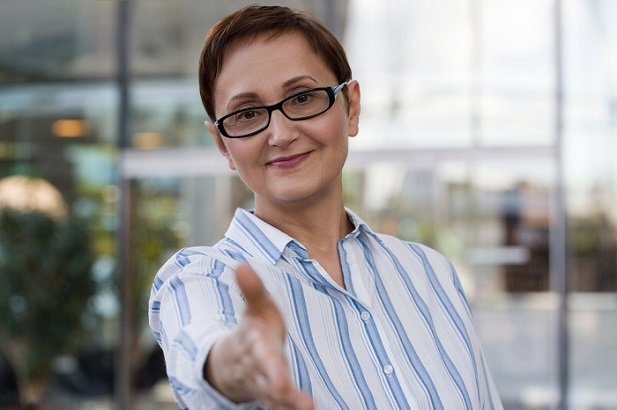 middle aged woman with glasses holding out hand to shake hands