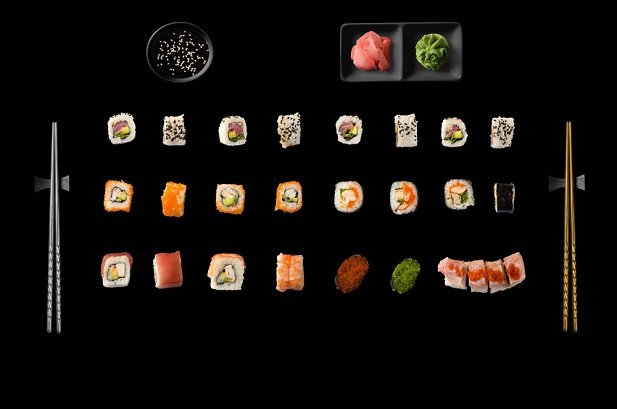 various types of sushi arranged in rows on black background