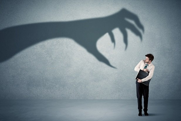 man cringing beneath shadow of giant claws