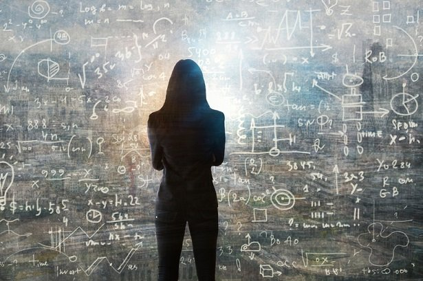woman standing in front of chalkboard filled with calculations