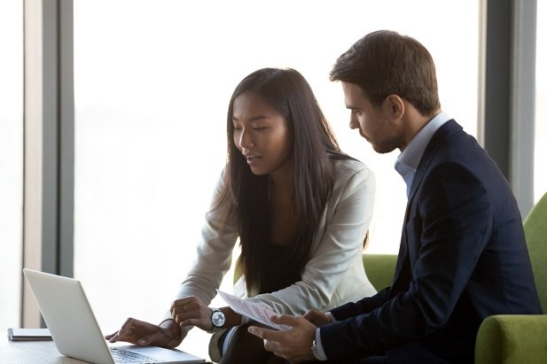young female advisor at computer with young man
