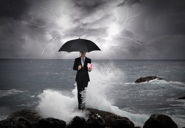 man on rocky shore in storm with umbrella