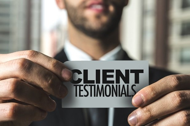 business man holding sign saying Client Testimonials