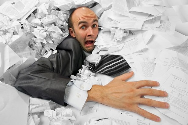 man drowning in papers