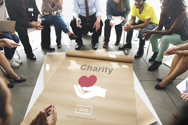 group of employees sitting around sheet of paper with charity on it and heart