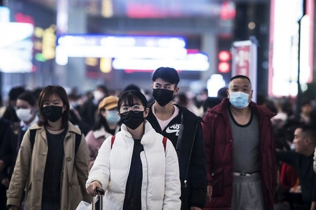 people on busy Shanghai street wearing face masks