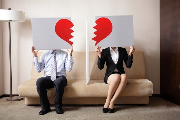man and woman holding signs with half a heart symbol