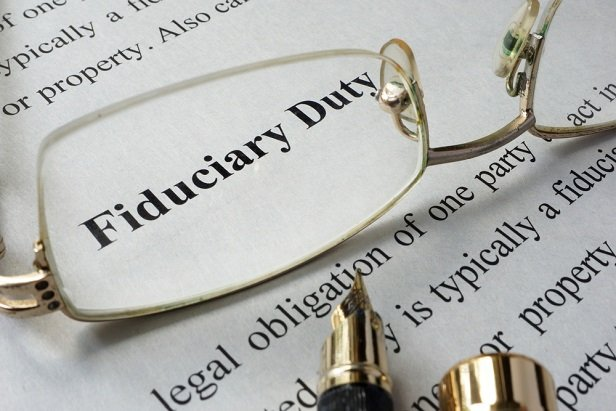 eyeglasses resting on dictionary with fiduciary duty defined