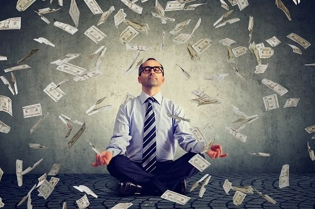 man meditating with money raining around him