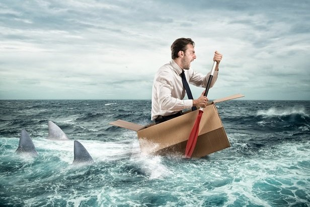 man in tie paddling boat being chased by sharks