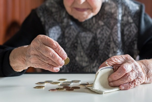 elderly woman's hands holding coins dumped from purse