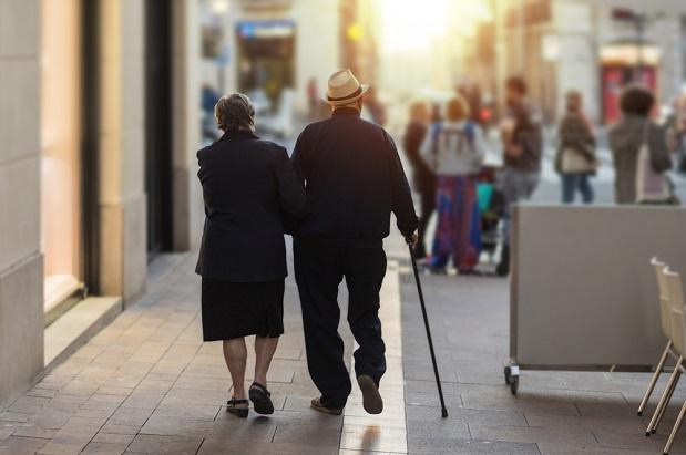 elderly couple walking down city street