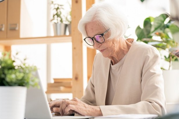 white haired older woman at computer