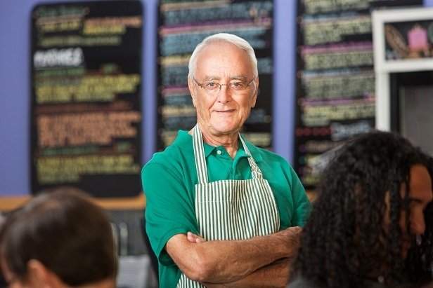 older man wearing butcher's apron smiling at camera