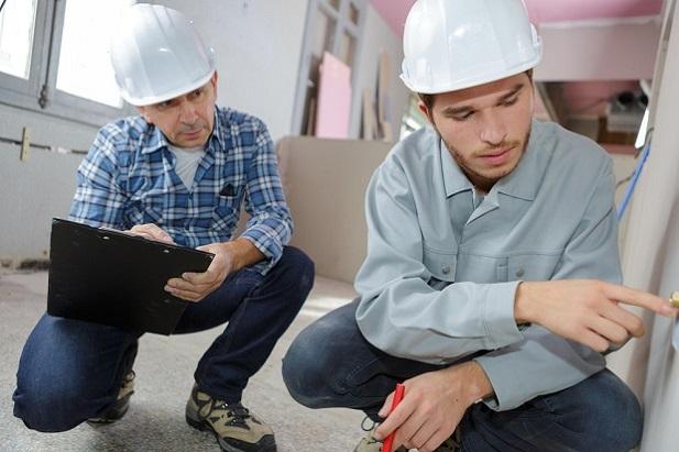 2 men in hardhats inspecting factory