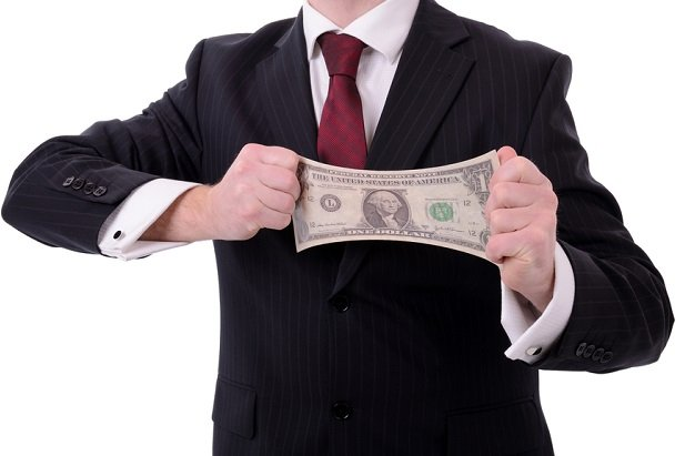 man in business suit stretching dollar bill