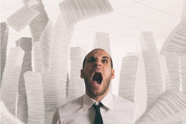 business man screaming as tax forms fly around him