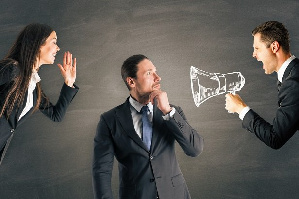 Businessman between man with megaphone and woman without