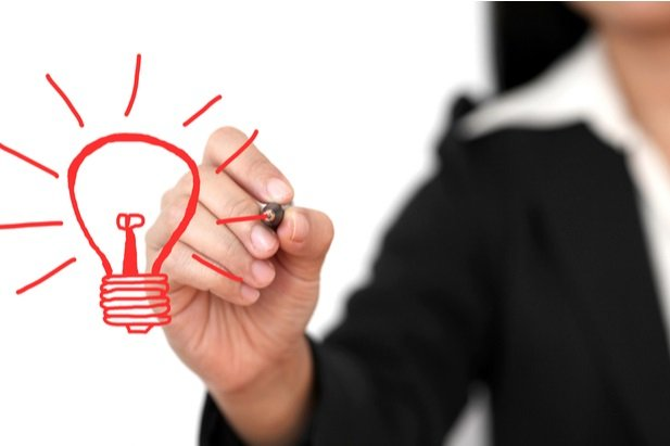 business woman in backgound drawing lighbulb in red marker on foreground