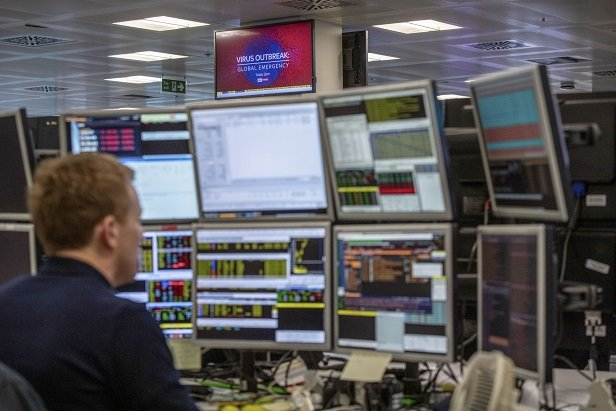 man at computer monitors watching stocks while coronavirus report plays on tv
