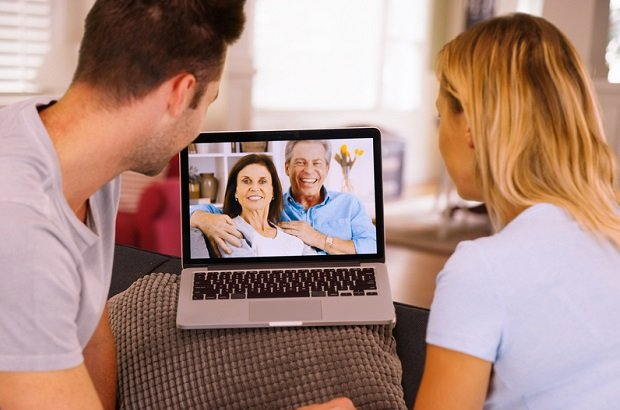 millennial couple facetiming on computer with boomer parents