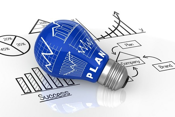 blue lightbulb with white charts on it, resting on paper with charts