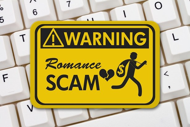 Sign on computer says Warning: Romance scam
