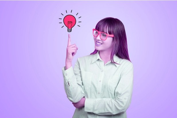 woman with colorful glasses holding colorful lightbulb balanced on her fingertip
