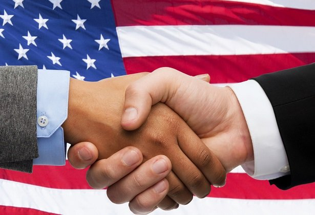 two people shaking hands in front of closeup of American flag