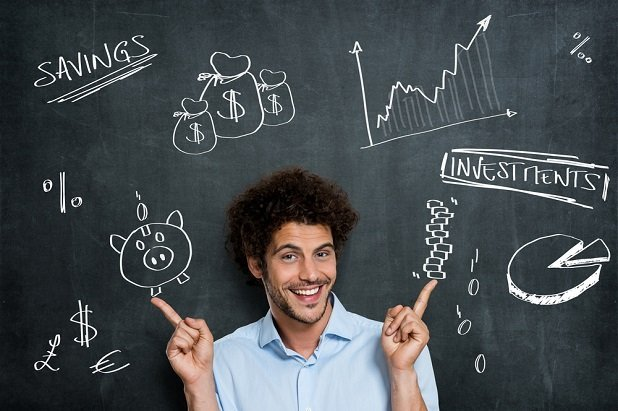 young man smiling in front of blackboard with investing and money symbols