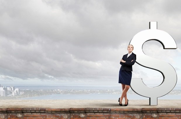 business woman leaning against giant dollar sign