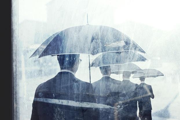 line of gray men holding gray umbrelllas in the rain