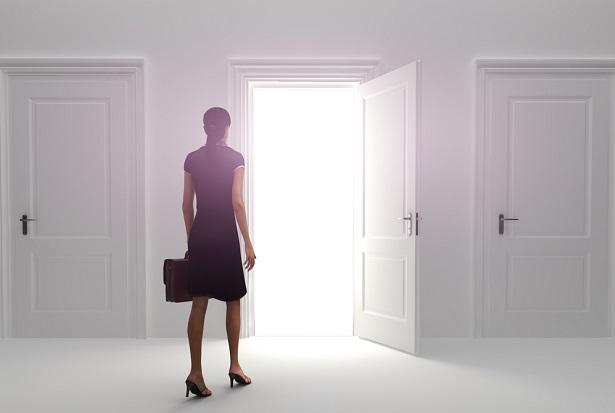 business woman with briefcase walking toward open lit doorway