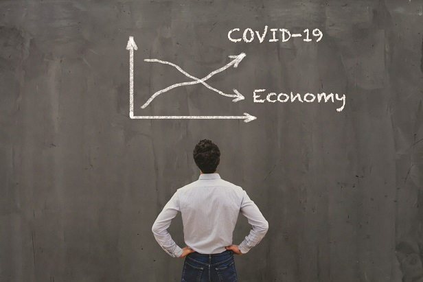 man staring at blackboard with covid arrow going up and economy arrow going down